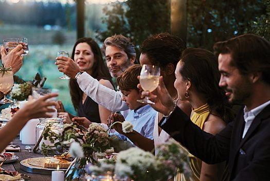 Group Dinner image with happy people raising a glass in toast