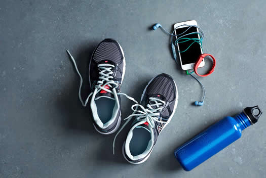 Pair of running shoes with an iPhone, headphones and a waterbottle